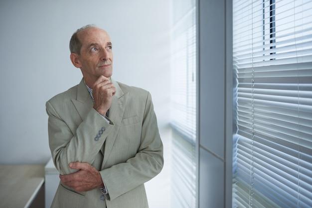 Maduro hombre de negocios caucásico en traje de pie junto a la ventana con persianas cerradas y mirando a otro lado