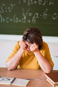 Maestra de alto ángulo en el escritorio cansado