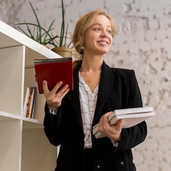 Maestra de ángulo bajo con pila de libros