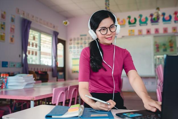 La maestra asiática de kindergarten está enseñando en línea a estudiantes de kindergarten. los maestros y los estudiantes usan sistemas de videoconferencia en línea para enseñar a los estudiantes.