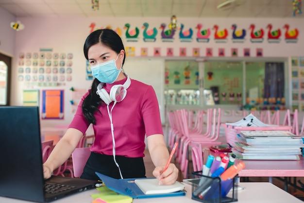 Maestra asiática con máscaras médicas que enseñan a estudiantes de jardín de infantes en línea los maestros y los estudiantes usan sistemas de videoconferencia en línea para enseñar a los estudiantes.
