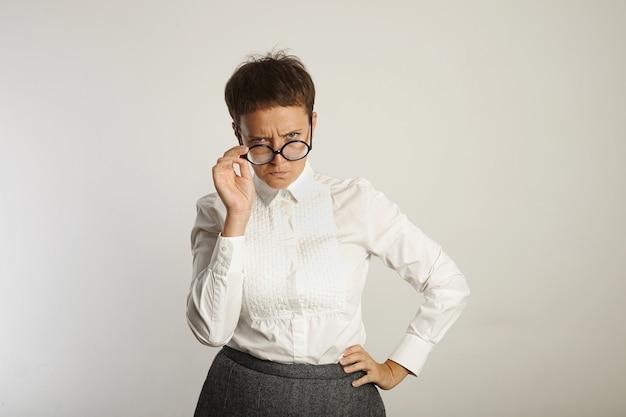 Maestra de aspecto severo en blusa blanca y falda gris mirando con desaprobación por encima de las gafas