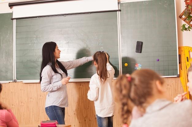 Maestra ayudando al alumno a resolver el ejemplo de matemáticas en la pizarra