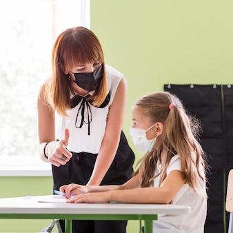 Maestra ayudando a su alumno en clase