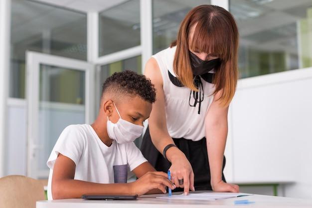Maestra ayudando a su alumno mientras usa máscaras médicas