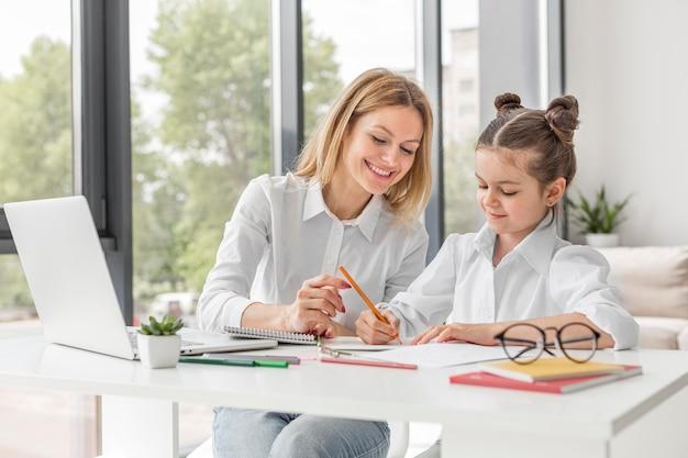 Maestra ayudando a su hija a estudiar en casa