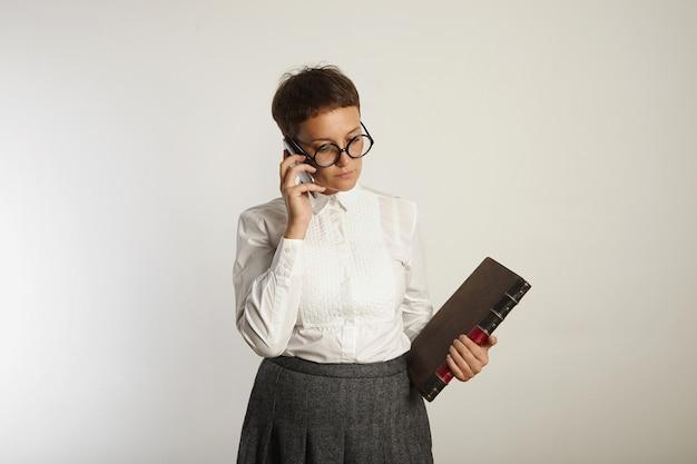 Maestra en blusa blanca y falda de tweed gris sostiene un libro viejo y habla por teléfono en blanco