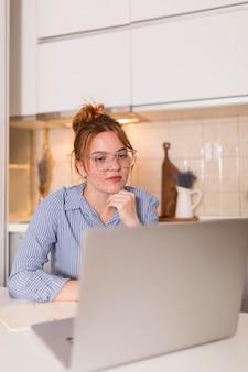 Maestra en casa escuchando a los estudiantes de la clase en línea