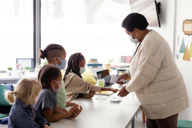 Maestra comprobando la temperatura de cada alumno