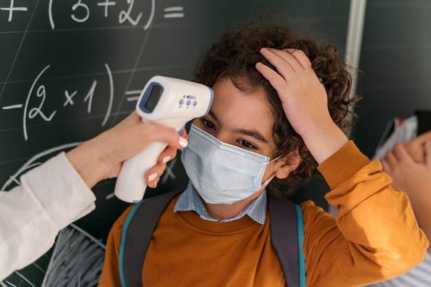Maestra comprobando la temperatura del estudiante en la escuela