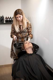 La maestra de corte de cabello lava el cabello de su cliente