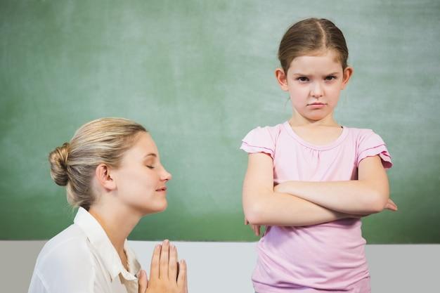 Maestra disculpándose niña en el aula