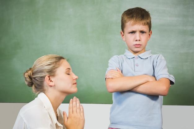Maestra disculpándose niño en el aula
