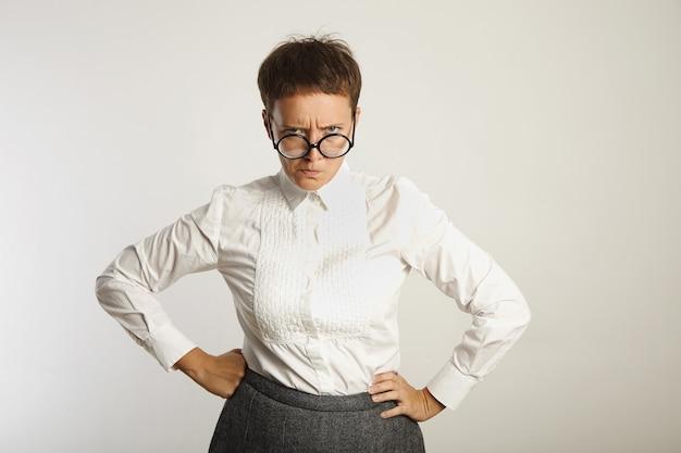 Maestra enojada en gafas negras redondas y traje conservador con el ceño fruncido aislado en blanco