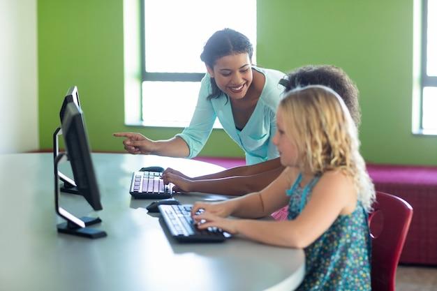Maestra enseñando computadora con niños