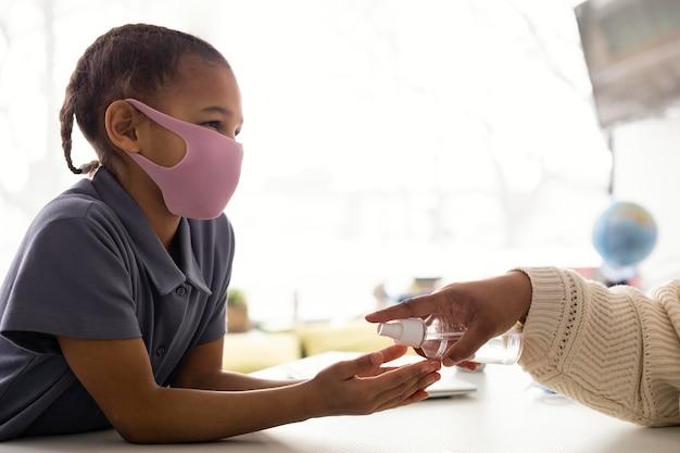 Maestra enseñando a los niños sobre la desinfección