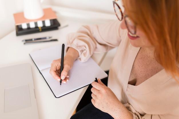 Maestra en el escritorio escribiendo en la agenda durante la clase en línea