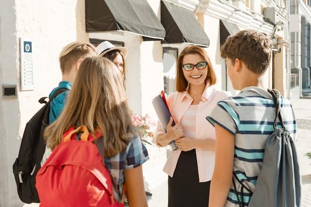 Maestra de escuela al aire libre con un grupo de estudiantes adolescentes de secundaria.