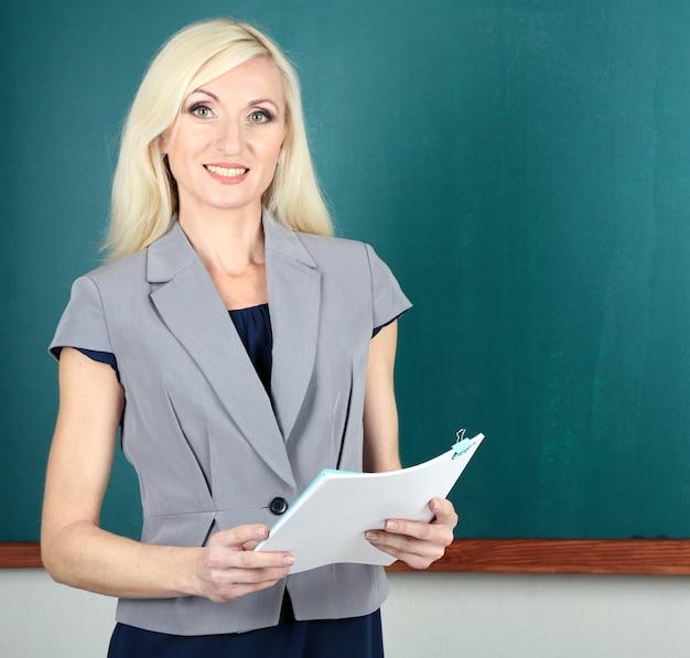 Maestra de escuela cerca de primer plano de la pizarra