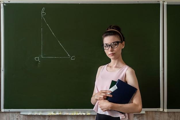 Maestra de escuela primaria cerca de la pizarra y dibuja un triángulo