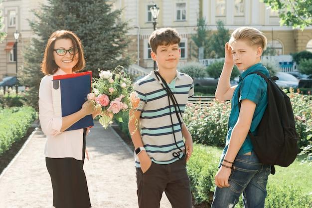 Maestra de escuela con ramo de flores y grupo de hijos adolescentes