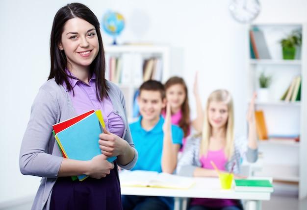 Maestra feliz con alumnos de fondo
