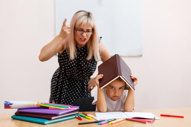 La maestra le grita a la pequeña colegiala