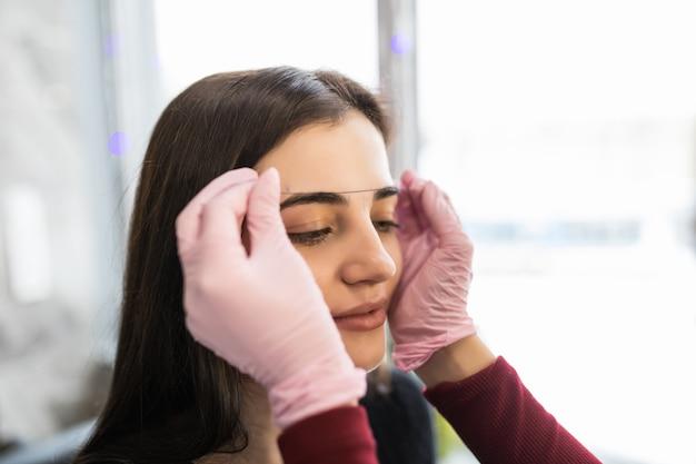 Maestra en guantes blancos revisa el contorno de las cejas con hilo