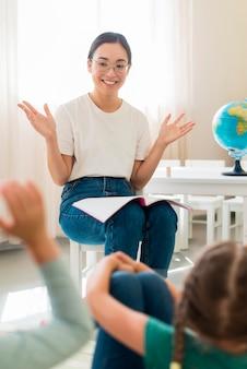Maestra haciendo preguntas para sus alumnos