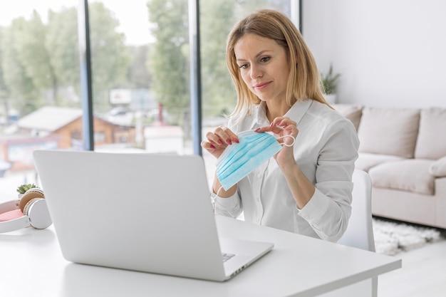Maestra haciendo sus clases en línea mientras sostiene una máscara médica