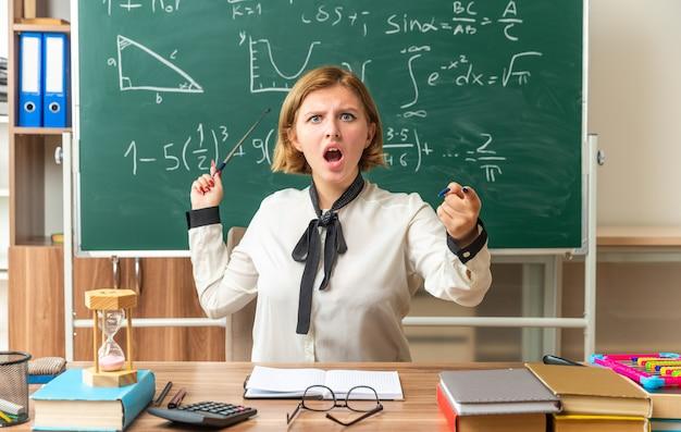 Maestra joven enojada se sienta a la mesa con puntos de herramientas escolares en la pizarra que le muestra gesto en el aula