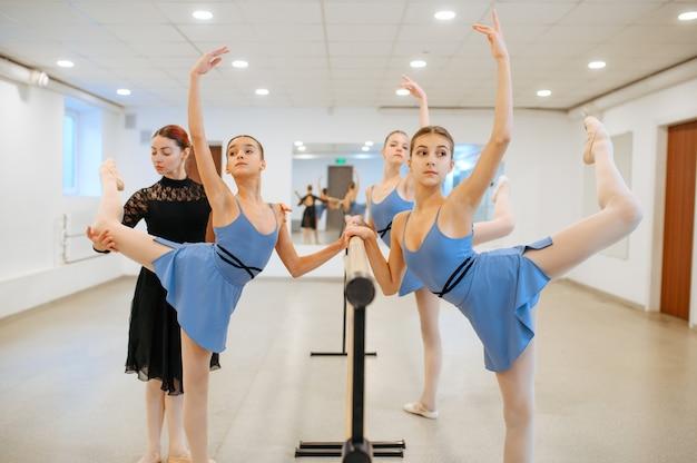 Maestra y jóvenes bailarinas se ejercitan en la barra en clase