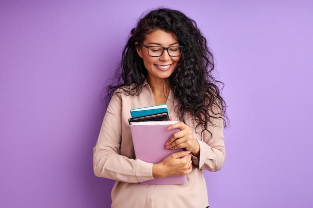 Maestra con libros en manos aisladas en la pared púrpura, señorita en anteojos disfrutar de la educación, reír