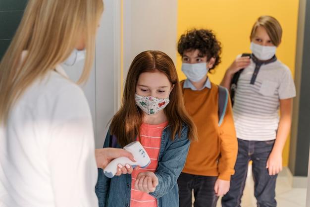 Maestra con máscara médica comprobando la temperatura del estudiante en la escuela