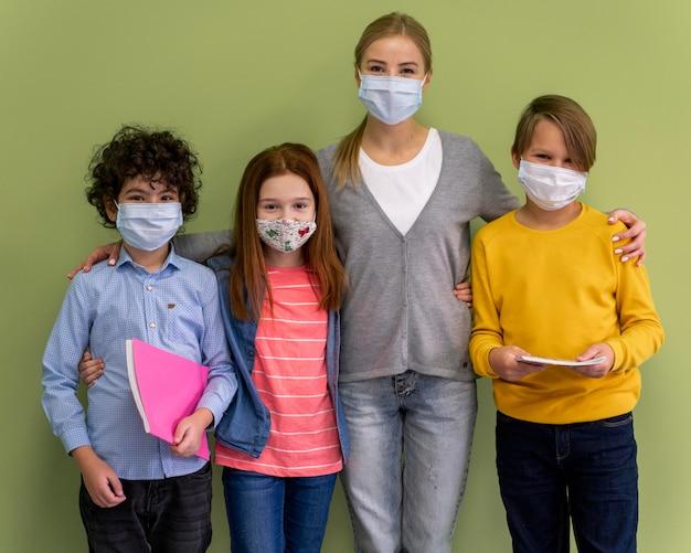 Maestra con máscara médica posando con niños en la escuela