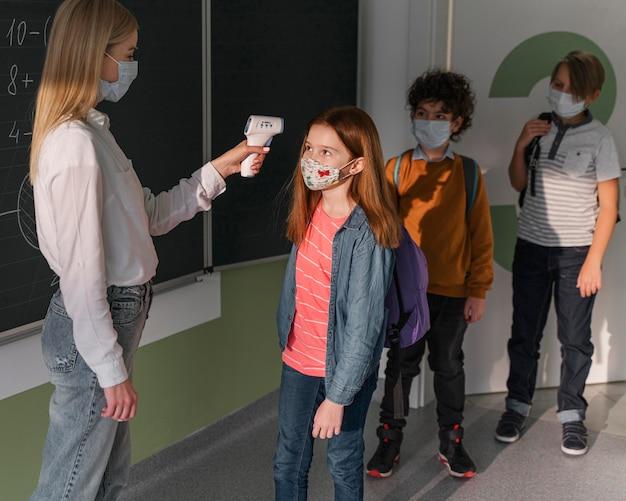 Maestra con máscara médica que controla la temperatura de los niños en la escuela