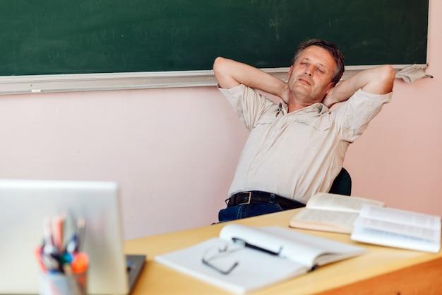 La maestra de mediana edad descansa en el aula y duerme.