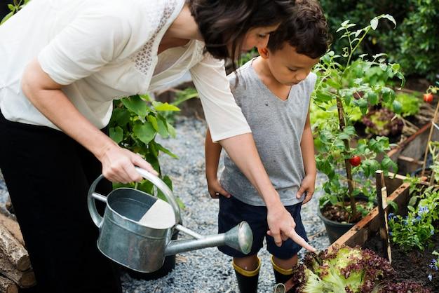 Maestra mostrando a su estudiante como regar las plantas