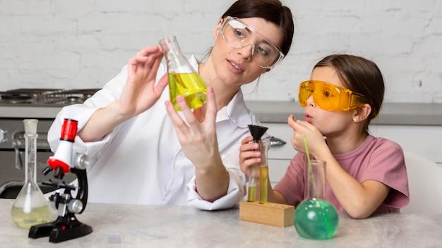 Maestra y niña haciendo experimentos científicos