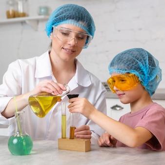 Maestra y niña con redecillas para el cabello haciendo experimentos científicos con tubos de ensayo