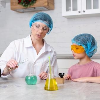 Maestra y niña con redecillas para el cabello haciendo experimentos científicos