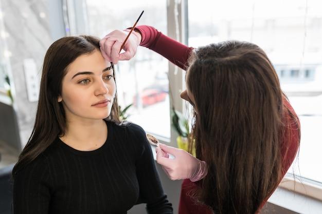 Maestra pone pintura de cejas con pincel durante el procedimiento de maquillaje