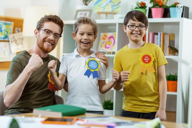 Maestra de primaria. los jóvenes estudiantes se inspiraron a estar felices con los resultados de sus trabajos mientras posaban con su gran maestro.