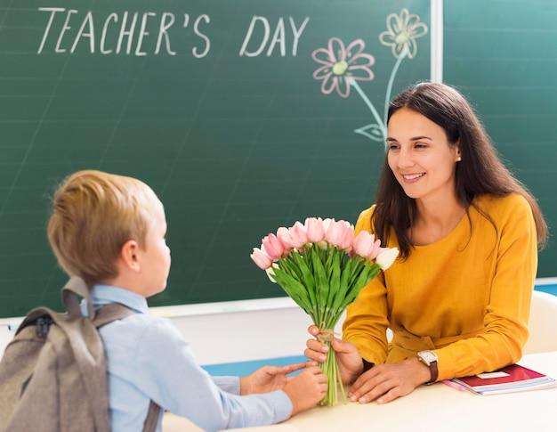 Maestra recibiendo flores de sus alumnos