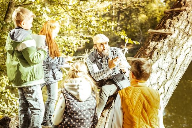 Maestra rodeada de estudiantes que enseñan sobre energías alternativas en un buen día.