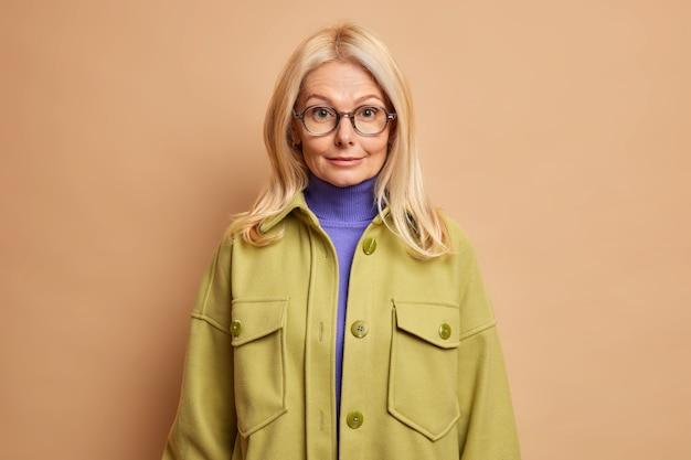 La maestra senior segura se viste para el trabajo, tiene cabello rubio, usa lentes transparentes con cuello alto y una elegante chaqueta para caminar al aire libre durante el día de otoño.