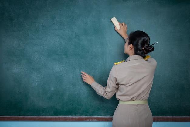 Maestra tailandesa en traje oficial borrando pizarra