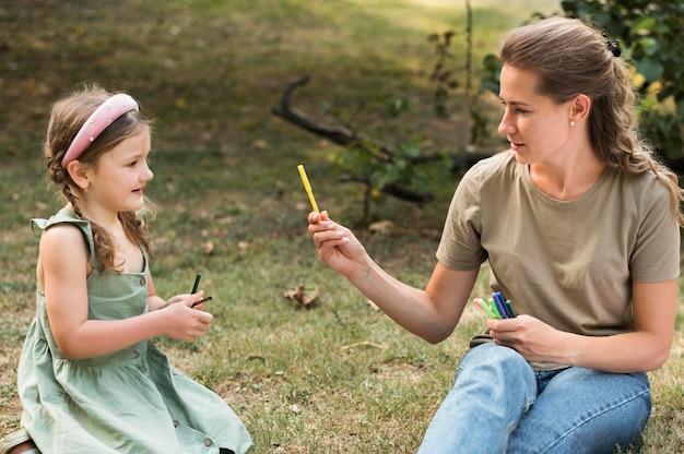 Maestra de tiro medio y niña con crayones
