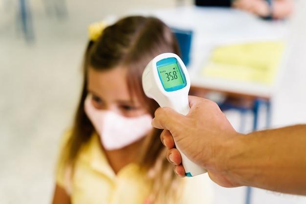 Maestra tomando la temperatura de una niña con un termómetro durante la pandemia de covid. ella no tiene fiebre, esta sana