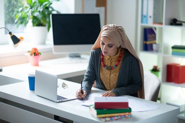 Maestra trabajadora. profesor musulmán trabajador ocupado sentado en la mesa y preparando la lección
